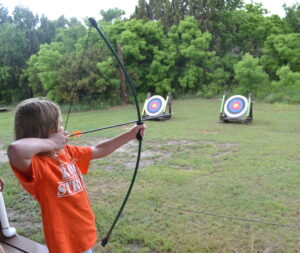 Kid shooting a bow and arrow at archery range